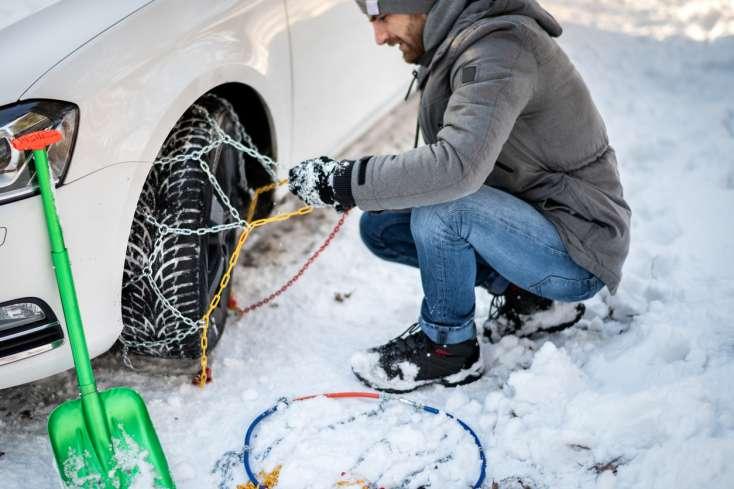 Homme qui installe des chaînes sur ses pneus neige